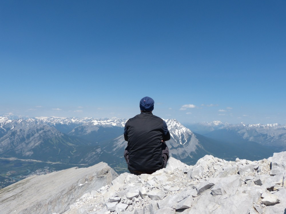 An Irishman on tour at summit of Mount Rundle in Canada